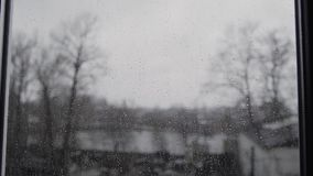 A heavy rain in summer in Germany - seen through the windowpane with the focus on raindrops. stock video footage