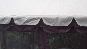 Heavy rain in the summer time under an awning. Rain storm on an awning. , strong rain falls, storm,. Strong rain falls, raindrop falling from the awning stock footage