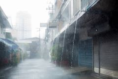 Heavy rain with town home. Waterfall from roof stock photography