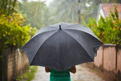Heavy rain. Woman with black umbrella in heavy rain Royalty Free Stock Photography