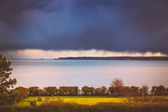 Heavy rainclouds over the horizon and Deal and Sandwich in Kent, Uk whilst the sunshine on a park area of the Royal Esplanade,. Ramsgate stock photo