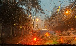 Raindrops and street light bokeh at night on car wind shield Royalty Free Stock Image