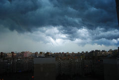 Heavy rainy clouds over city. Typical modern residential distric Stock Photos