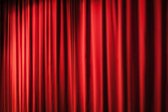 Heavy red curtains. A closed red stage curtain in a small theater royalty free stock images