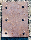Heavy rusted steel plate with six bolts. Royalty Free Stock Images