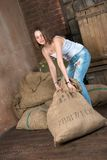 Heavy sack. Young woman in dilapidated warehouse lifts heavy sack stock image