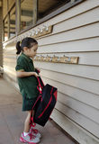Heavy School Bag. A young schoolgirl lifts up her heavy school bag to hang on the hook royalty free stock photography