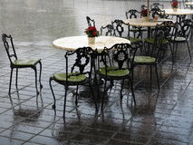 Heavy shower abandoned alfresco bistro. Victorian era style furnishings of an alfresco bistro abandoned by a heavy shower Stock Photos