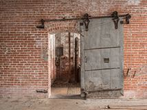 Heavy sliding metal industrial door in old warehouse. Heavy sliding industrial door in old warehouse with pipes and ladder against a brick wall with wooden Royalty Free Stock Photos