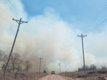 Heavy smoke from a wildfire in a rural area. Crossing the road, cutting off the road Stock Images