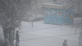Heavy snow falling in city on background of kiosk stock video