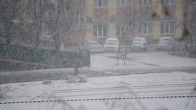Heavy snow falling in city. Urban landscape with heavy snow falling in city with one car moving and one man walking stock video footage