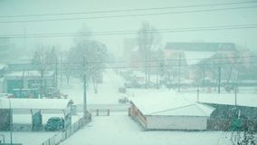 Heavy snow falling in winter on a road of small town. Heavy snow falling in winter on a street of a small country town stock footage