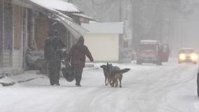 Heavy snow on the street. Snowstorm, people walking down the street in heavy snow stock video footage