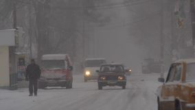 Heavy snow on the street. Snowstorm, people walking down the street in heavy snow stock footage