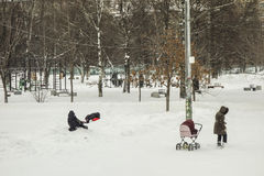 In heavy snow woman and two children playing near a block of fla Stock Photos