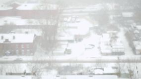 Heavy snowfall in the city in slowmotion. Streets, houses and machine Snowy. Changes focus from blurred. 1920x1080 stock video footage