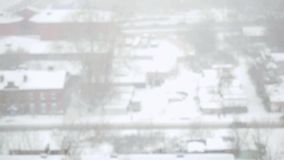 Heavy snowfall in the city in slowmotion. Streets, houses and machine Snowy. Changes focus from blurred. 1920x1080 stock video