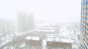 Heavy snowfall in the city in slowmotion. Streets, houses and machine Snowy. Changes focus on blurred. 1920x1080 stock footage