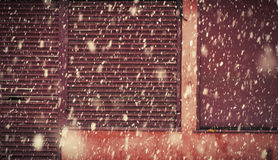 Heavy snowfall on a city street in the winter in Manchester Levenshulme England. Red garage door stripped texture, metal. Background royalty free stock photos