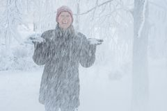 Young woman in the city in the snow. Heavy snowfall in the city and a young woman standing under the falling snow Stock Images
