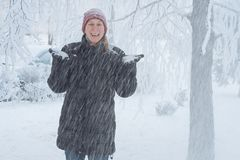 Young woman in the city in the snow. Heavy snowfall in the city and a young woman standing under the falling snow Royalty Free Stock Photos