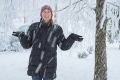Young woman in the city in the snow. Heavy snowfall in the city and a young woman standing under the falling snow Stock Image