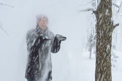 Young woman in the city in the snow. Heavy snowfall in the city and a young woman standing under the falling snow Stock Photography
