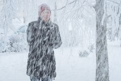 Young woman in the city in the snow. Heavy snowfall in the city and a young woman standing under the falling snow Stock Photo
