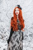Heavy snowfall. Girl with long red hair on winter background. Beautiful redhead retro woman in black retro dress and with long glo royalty free stock image