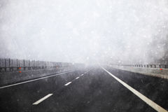 Heavy snowy and foggy winter highway road background. With no cars. Danger heavy snowfall empty road background with copyspace. Conceptual photo stock image