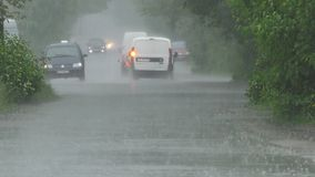 Heavy rain in spring. Heavy spring rain floods the streets with cars on the road and people passing by stock video footage