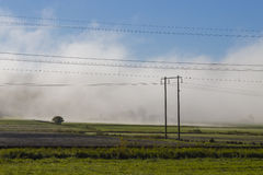 Heavy steam rising from the fields. Heavy steam rising from the newly ploughed fields as the morning sun heats how the ground, almost covering the farm buildings Royalty Free Stock Photo
