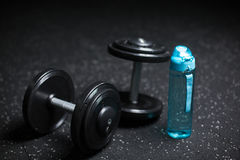 Heavy steel dumbbells, a blue bottle for water, equipment for sports routine on a dark blurred background. Royalty Free Stock Images