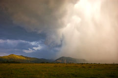 Heavy storm coluds with rain falling over the meadow Royalty Free Stock Photos