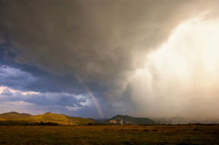 Heavy storm with rain and rainbow over the mountains Royalty Free Stock Image