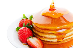 Heavy on the syrup. Pancakes and strawberry with heavy amount of maple syrup poured on top Stock Photo