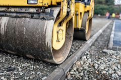 Heavy tandem road roller compacting layers of gravel on road construction site. Royalty Free Stock Photography