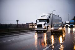 Heavy traffic with big rig semi trucks and another cars on highway in rain evening. Heavy traffic with big rig semi trucks convoy with semi trailers transporting royalty free stock photography