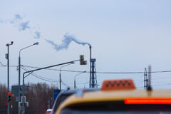 Heavy traffic in the direction of smoking pipe of oil refinery. Stock Photos