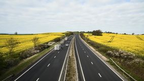 Heavy traffic on rural motorway among blooming rapeseed field. Speeding vehicles on busy rural motorway at bright sunny day. Time lapse sequence with sound of stock video footage