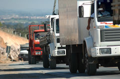Heavy_traffic_small_road. A cue of trucks follow slowly uphill as the traffic crawls in a hot summer day Royalty Free Stock Photo
