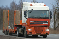Heavy truck DAF series XF with trailer for transportation of construction equipment close-up on the road Stock Images