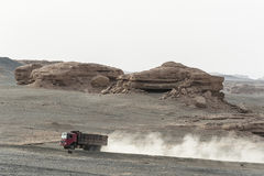 A heavy truck passing Yardang landform Stock Photo