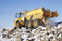 Heavy truck in rough terrain. Giant heavy truck driving in rough snowy terrain, rocks delivery Royalty Free Stock Images