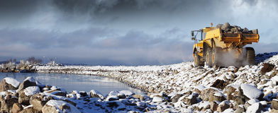 Heavy truck in rough terrain. Giant heavy truck driving in rough snowy terrain, rocks delivery. panoramic view Stock Photos