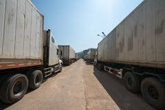 Heavy trucks loaded with goods trailers, parked in waiting area on state border crossing in Vietnam.  stock photo
