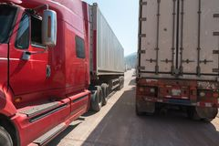 Heavy trucks loaded with goods trailers, parked in waiting area on state border crossing in Vietnam.  royalty free stock photography