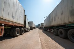 Heavy trucks loaded with goods trailers, parked in waiting area on state border crossing in Vietnam.  royalty free stock photo