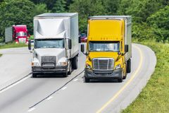 Two Semis Lead Traffic Down An Interstate Highway Royalty Free Stock Photos